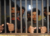 Indian fishermen stand in a police locku
