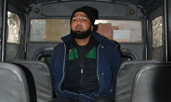 Malik Mumtaz Hussain Qadri, the bodyguard arrested in the shooting death of the Governor of Punjab Salman Taseer, is seen here detained in a police vehicle at the scene of the crime in Islamabad