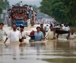 Residents carry their belongings through a flooded road in Risalpur in Pakistan's Northwest Frontier Province