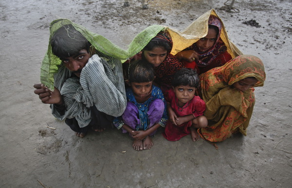 Family members, displaced by floods, use a tarp to escape a monsoon downpour while taking shelter at a make-shift camp for flood victims in the Badin district